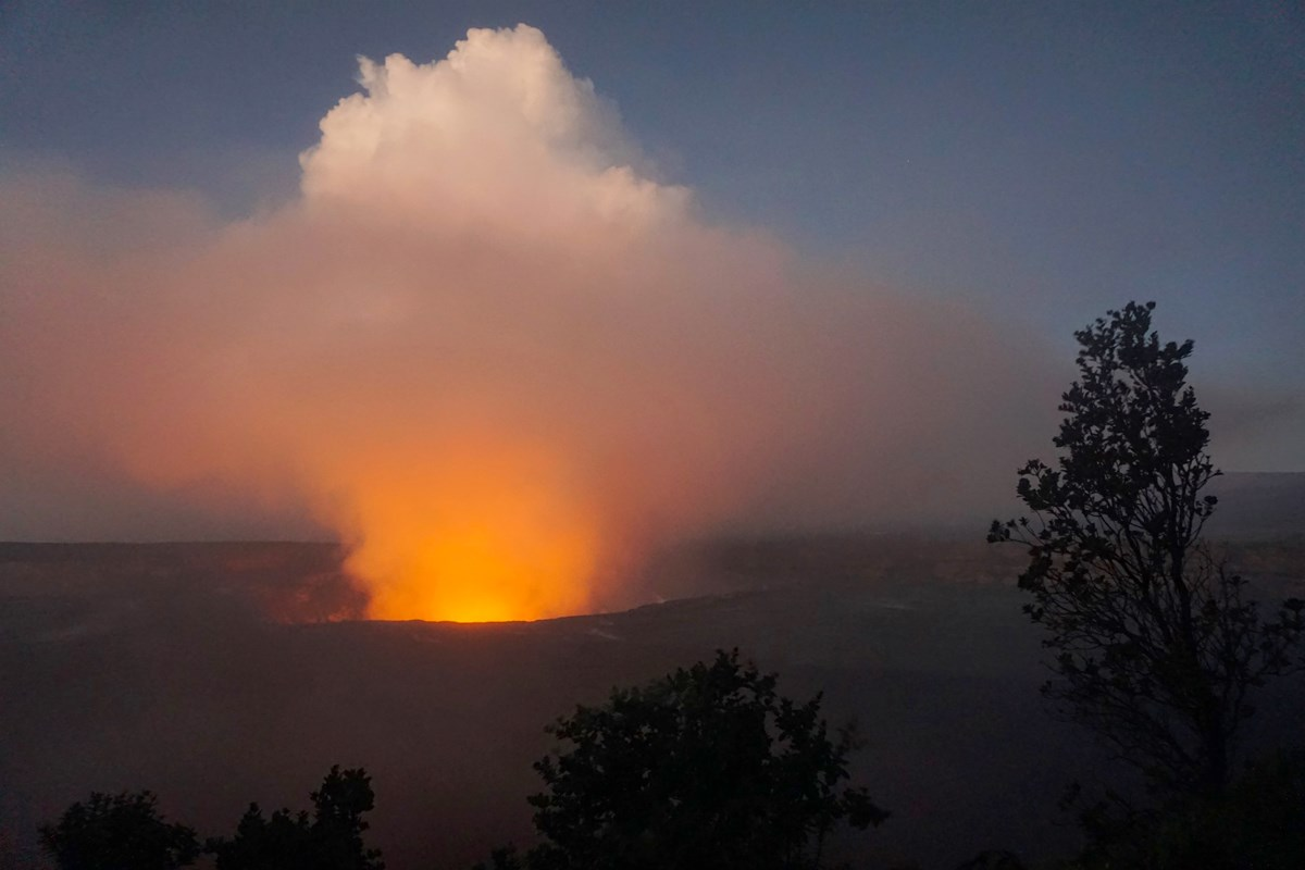 Glowing plume from an erupting volcanic caldera with tree silhouettes in the foreground