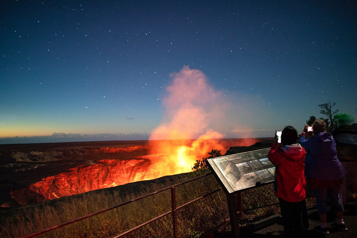 Two people standing at an overlook toward an erupting volcanic crater at night