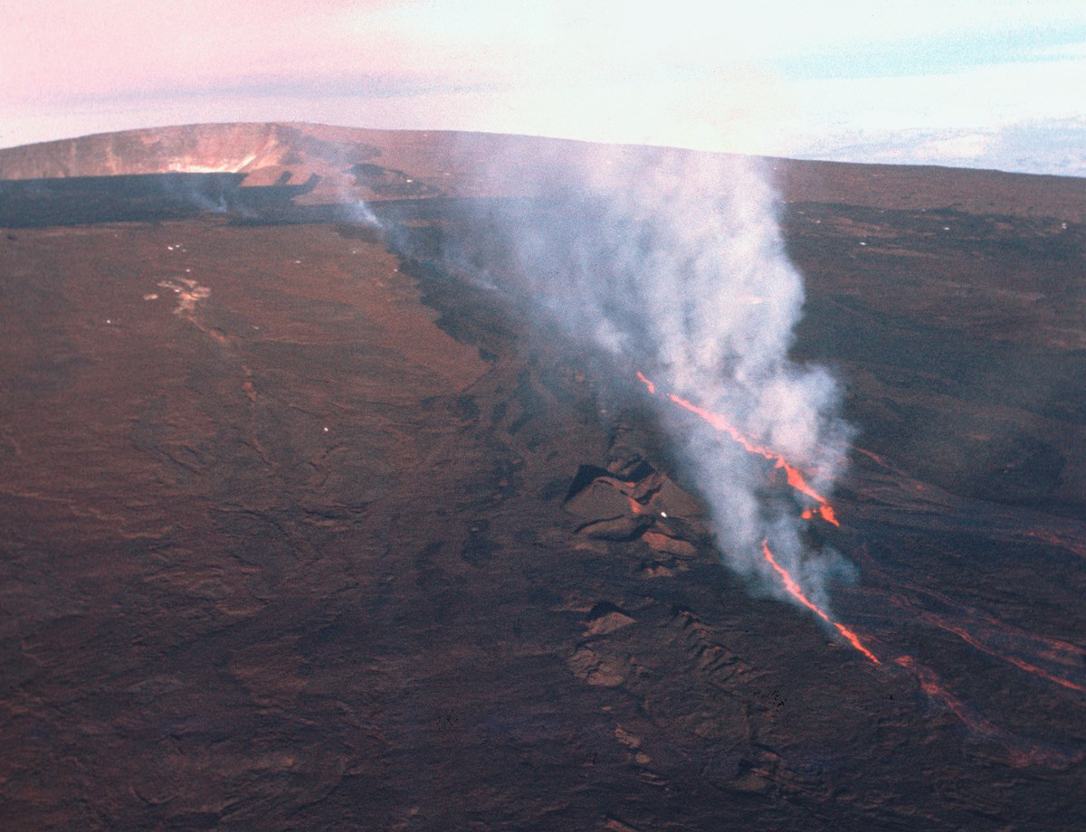Aerial view of a volcanic fissure spewing lava with a large volcanic caldera in the background