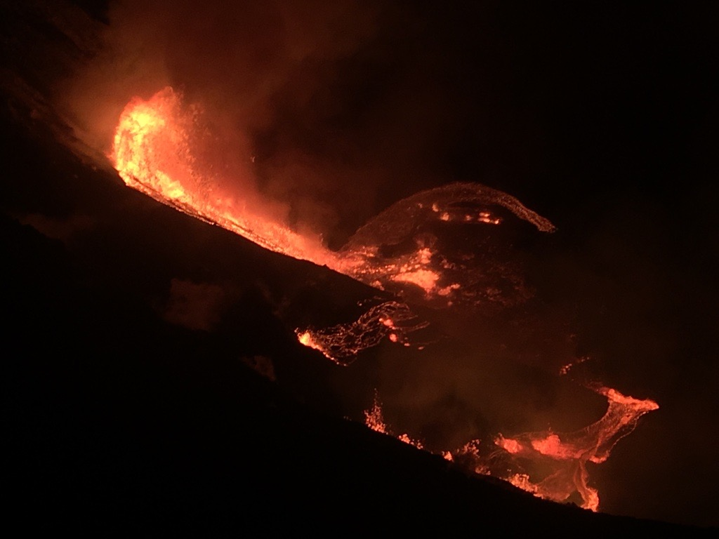 Lava cascading down into a crater at night, viewed from above