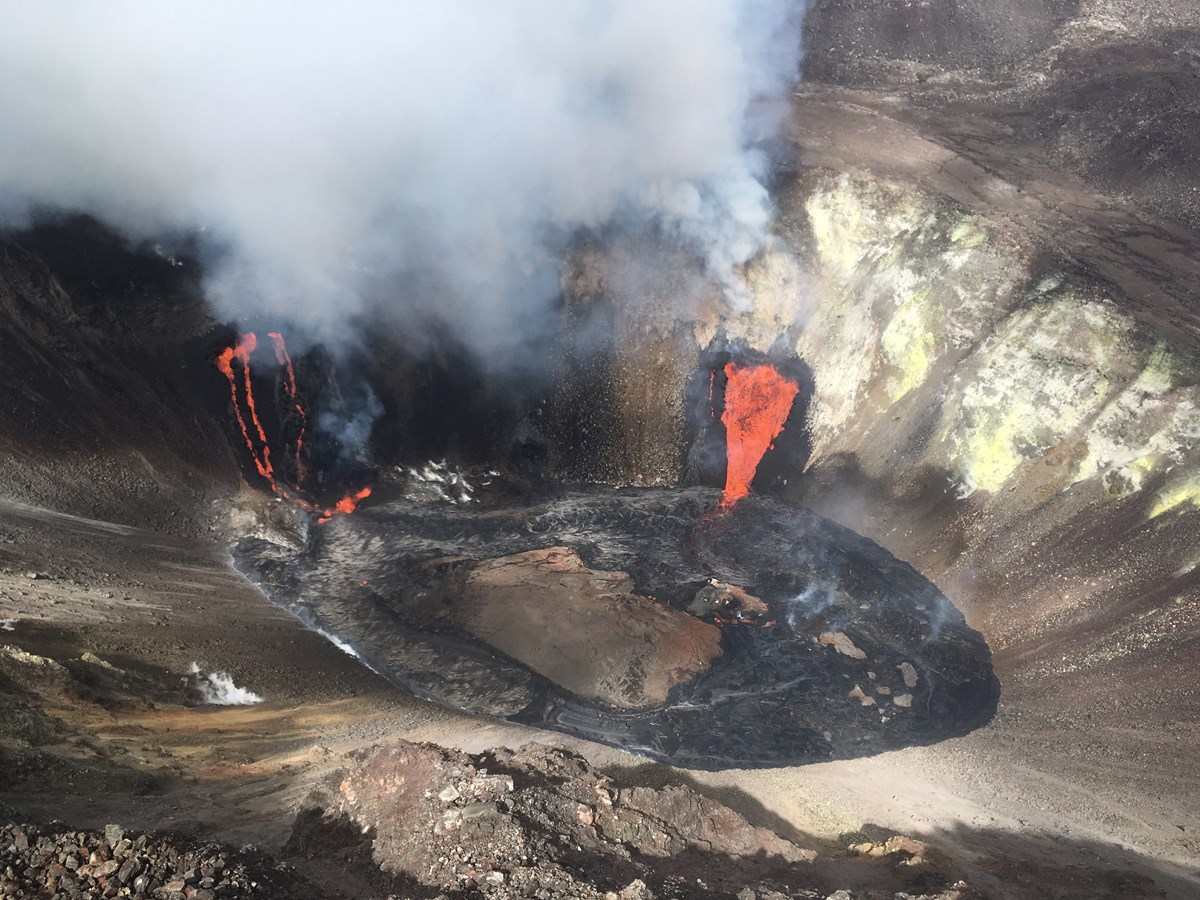 Aerial view of a volcanic crater with three streams of lava and yellow sulfur deposits