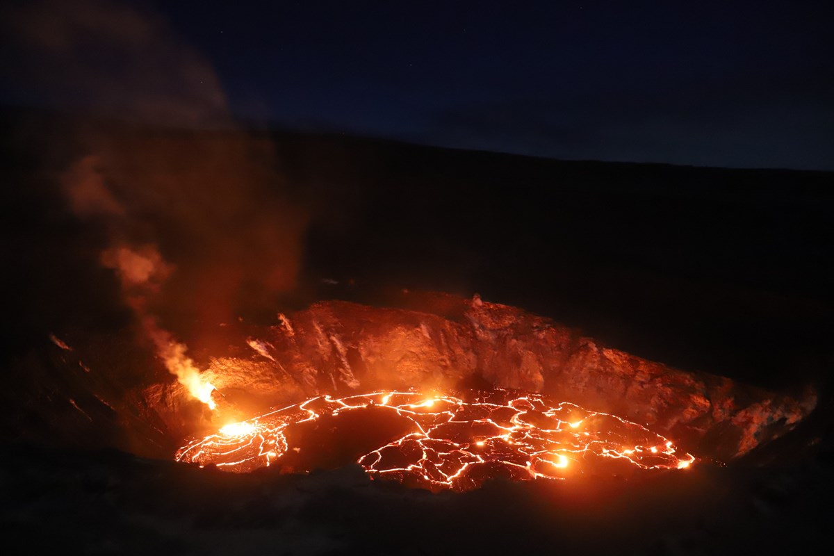 Glowing lava lake in a volcanic crater at night