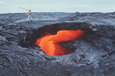 A hole in a solidified lava flow with glowing molten lava underneath, a man walks on top of the solidified flow