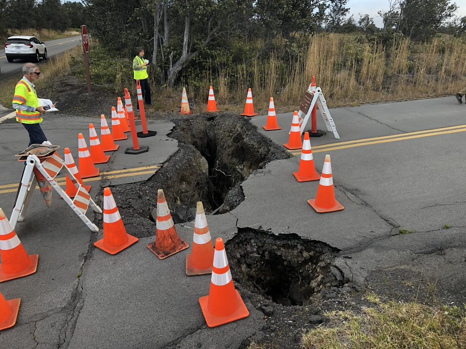 Workers contemplate earthquake damage to road