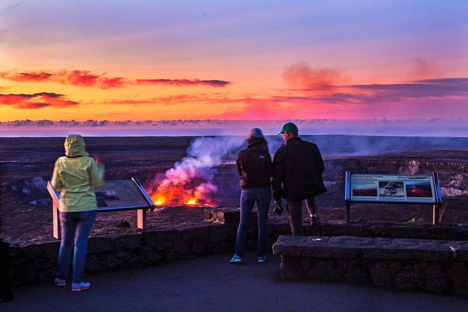 Visitors enjoy a rosy glow of sunrise and the glowing lava lake at Kīlauea summit