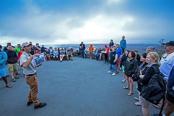 NPS Volunteer Marius Arigot gives a talk at Jaggar Museum Overlook to a crowd of visitors