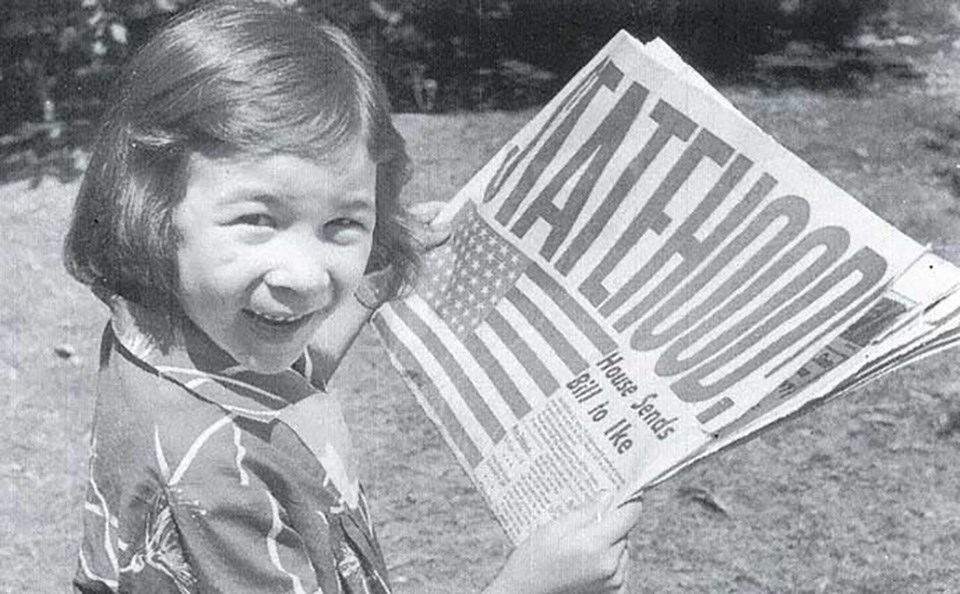 Child holding Hawai'i Statehood newspaper