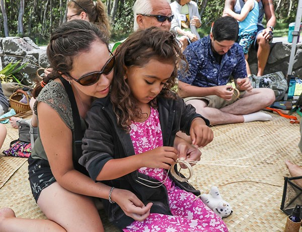 A youngster learns to weave lau hala bracelet at the 2017 Cultural Festival
