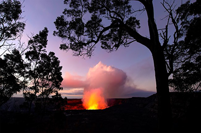 Through trees a red glow from lava illuminates the crater