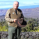 A man stands in old fashioned clothing at the edge of a volcano