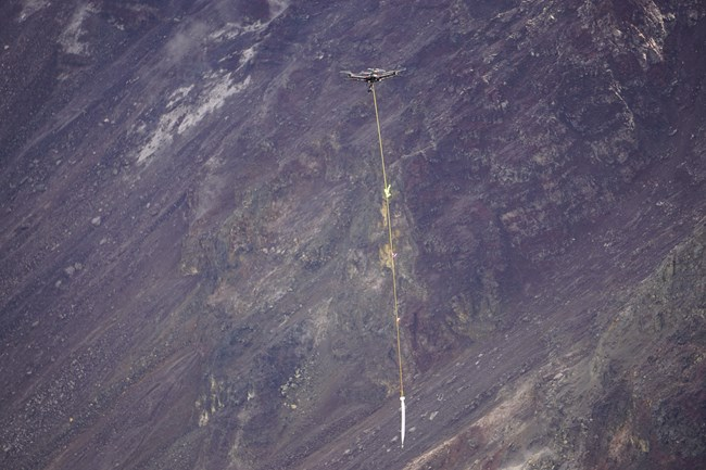 An unmanned aircraft system carrying a water container hanging by rope in a volcanic crater