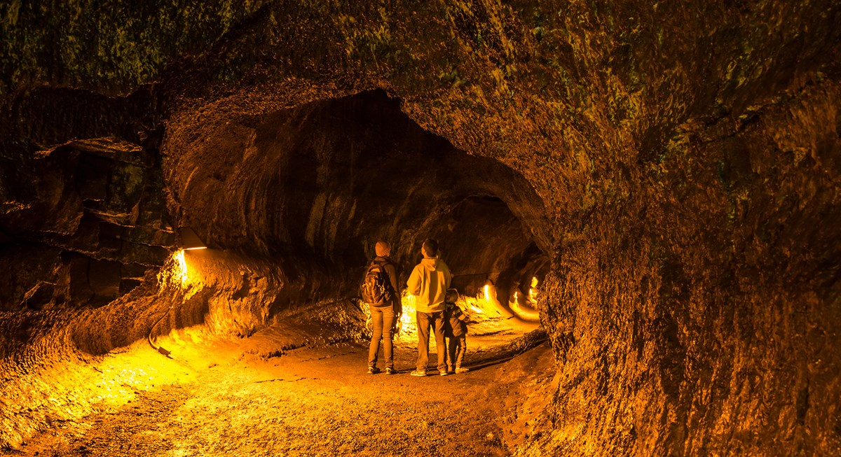 Park visitor standing in a lit lava tube