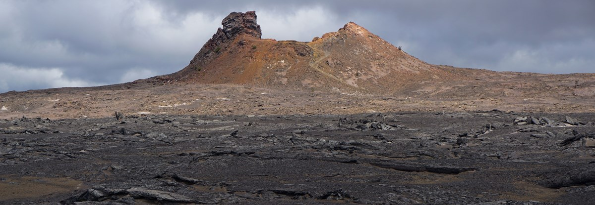 A sunlit cinder cone in a gray volcanic landscape
