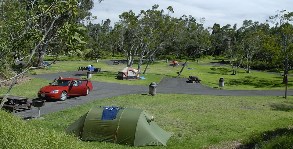 A and open and grassy campground with tents set up and a parked red car