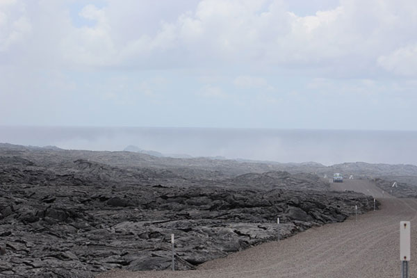 The presence of volcanic gas increases the closer you get to the ocean entry. This is where the lava crossed the Chain of Craters emergency access road, hiking in from the park side (USGS vehicle). Notice how the plume is blown right over the coastal area
