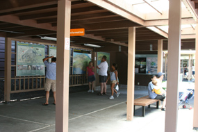 Visitors look at maps and information in the patio of the Kīlauea Visitor Center