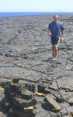 Drew crosses the pahoehoe lava, following the ahu (cairns).
