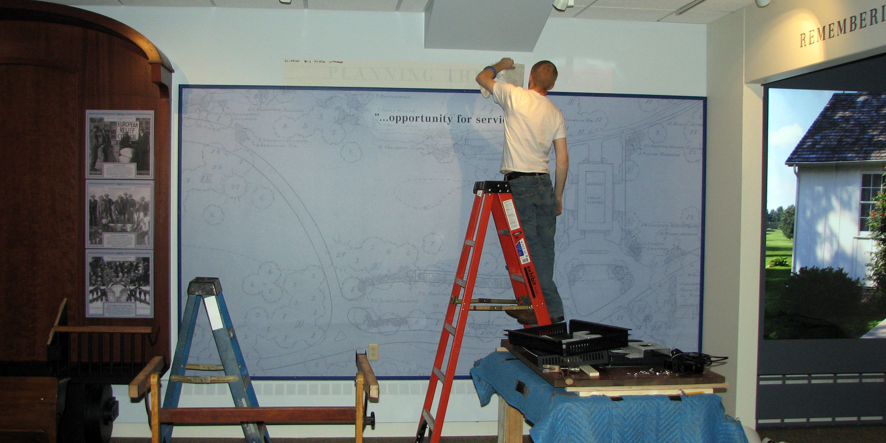 A man on a ladder stencils a heading on a museum exhibit under construction.