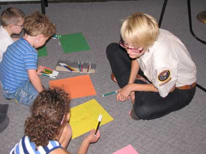A woman helps pre-school children write poems with markers and construction paper.