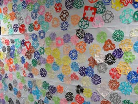 Cut paper flower patterns of different colors pasted on a schoolroom wall.