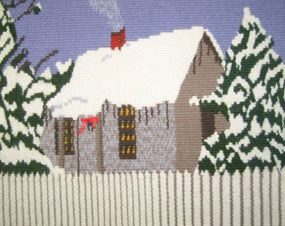 Hand-woven tapestry of a small wooden cottage behind a picket fence with a snow covered roof and flanked by snow-frosted trees.