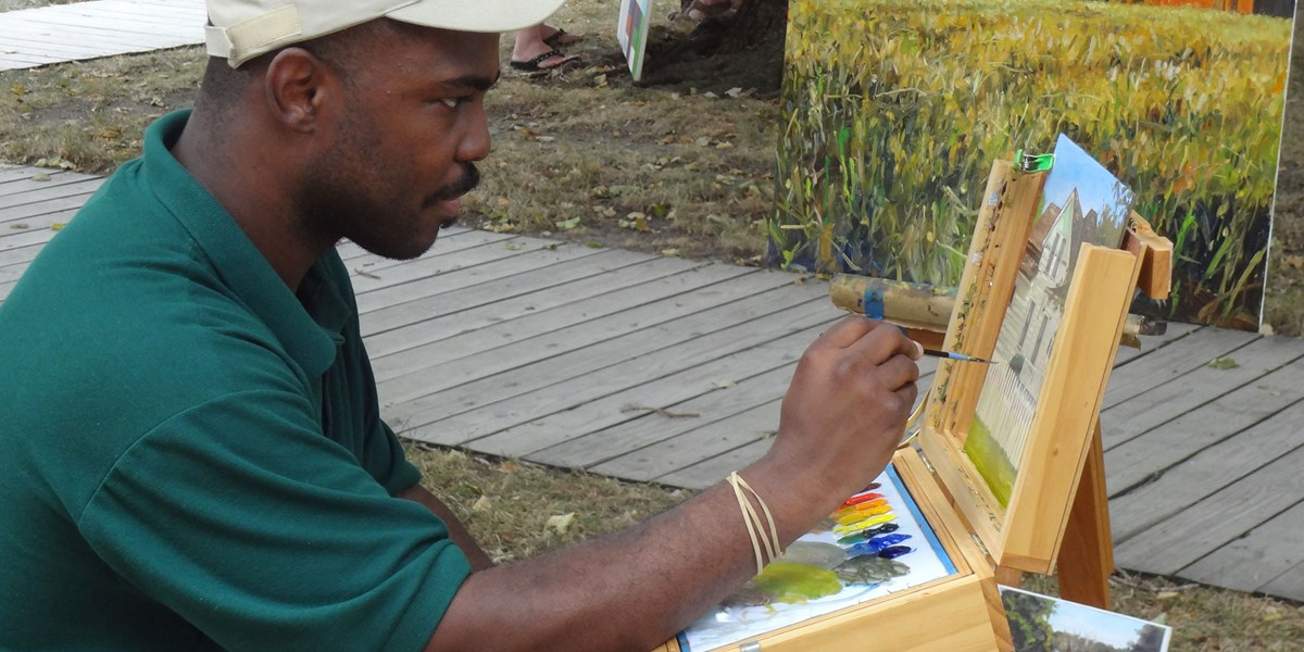 A man seated at an easel paints and displays finished paintings.