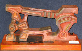 Orange ceramic sculpture of a floor-mounted iron cutting blacksmith tool.