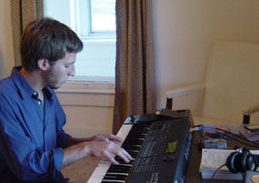 A young man wearing a blue shirt plays on an electric keyboard.