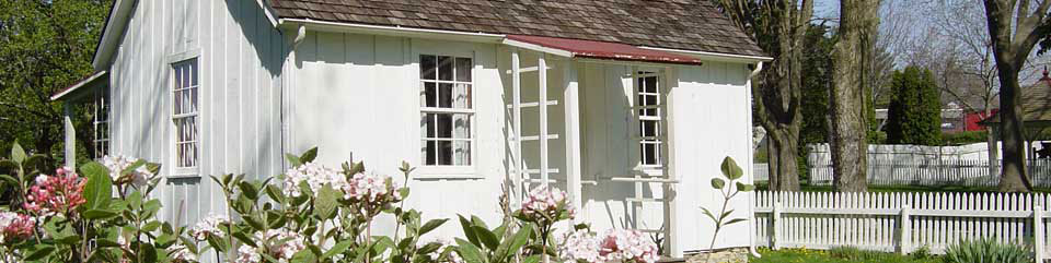Pink flowers blossom in the garden of a white two-room cottage.