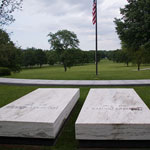Two marble grave stones and a flag overlook a park vista.