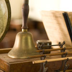 Pencils, books, a hand bell, and a globe sit atop a schoolhouse desk.