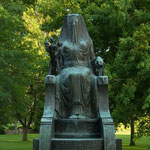 A bronze statue of an Egyptian goddess sits among park greenery.