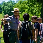 A park ranger with school children on a park field trip