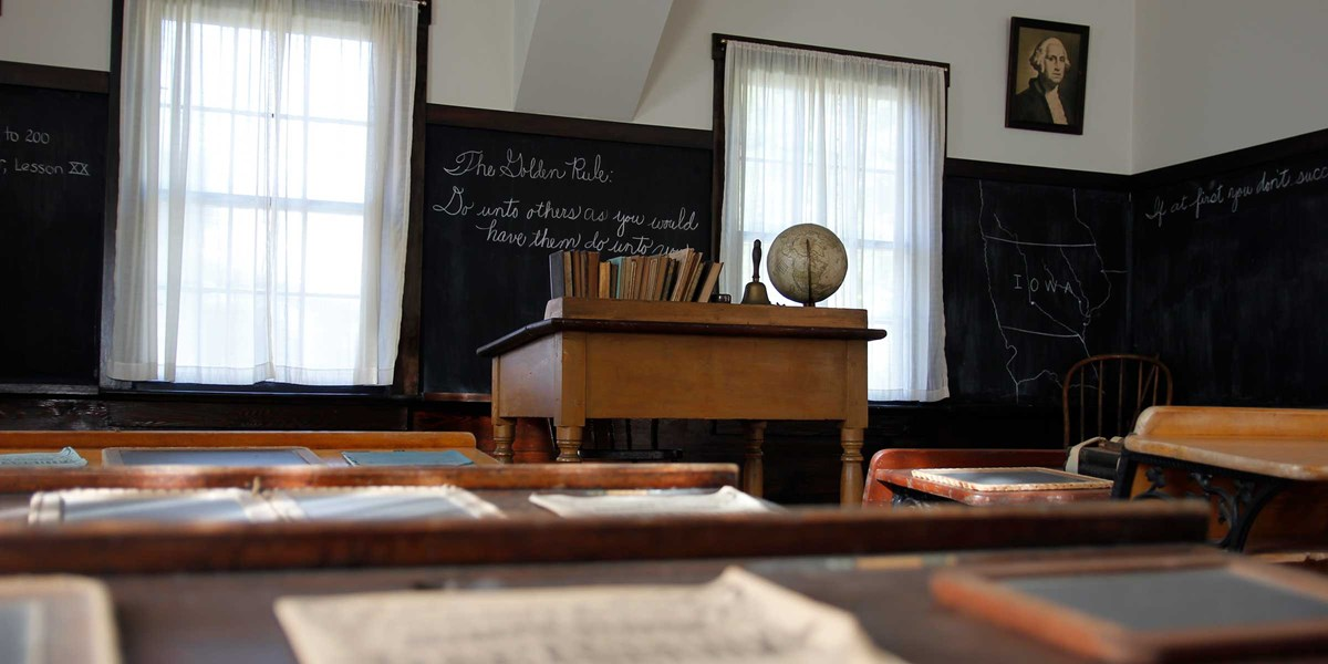 The teacher's desk in a restored 1870s classroom is seen from a pupil's desk.