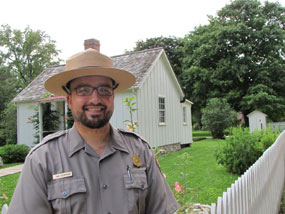 A male park ranger stands in front of a small white cottage.