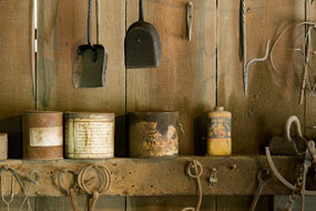 Cans of grease and shovels furnish the walls and shelves of an old-fashioned blacksmith shop.