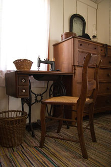 A chair and sewing machine next to a dresser and a window.