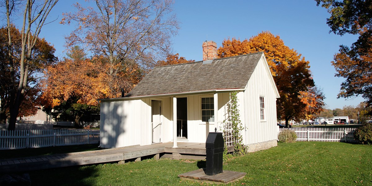 A small white cottage has a back porch with a wheelchair ramp and an old-fashioned pump nearby.