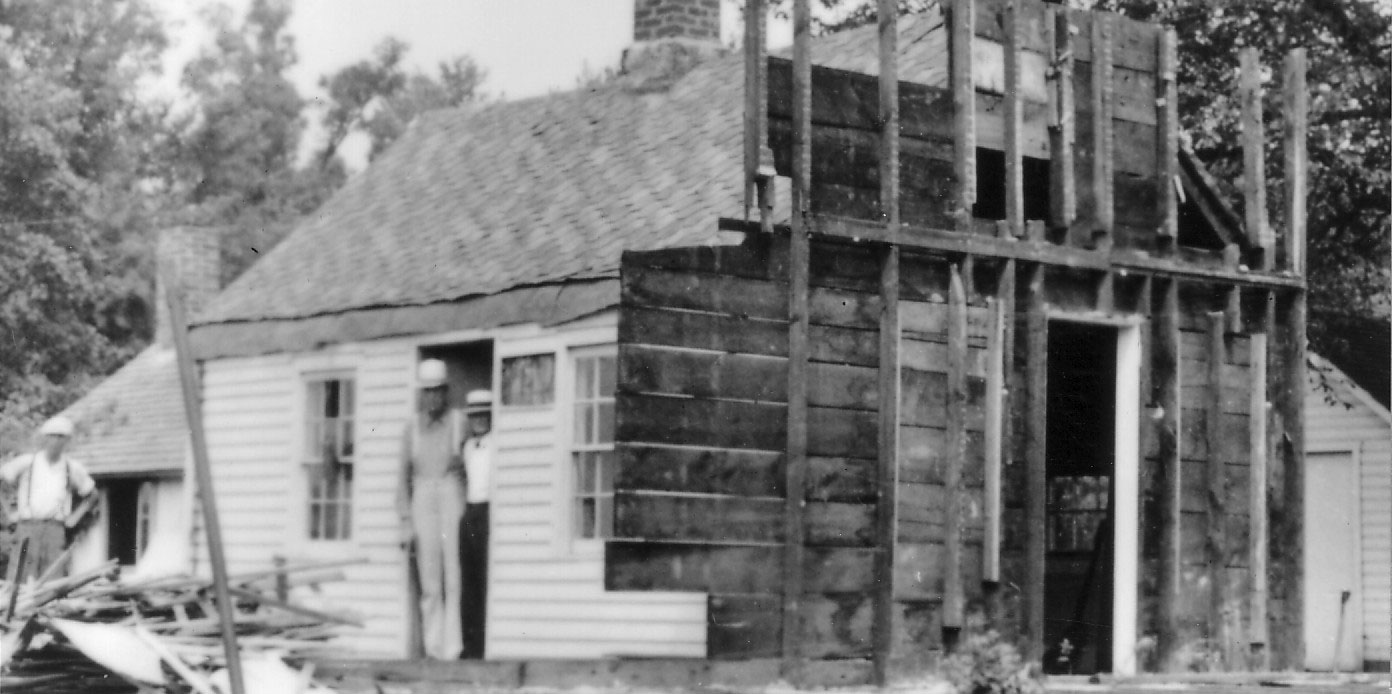 Workers pose by a small house under restoration.