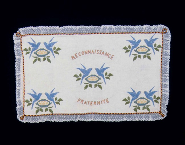Embroidered cloth from a flour sack depicts blue birds with the words Reconnaisance and Fraternite.