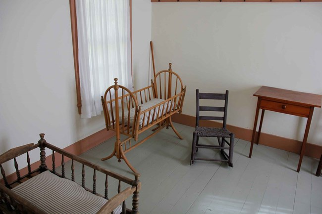 Antique rocking chairs and cradles furnish a small room.