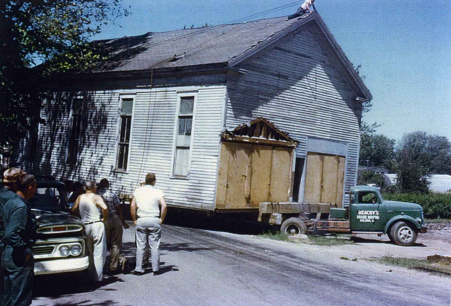Men watch as a pick-up truck moves a wooden building down a road.