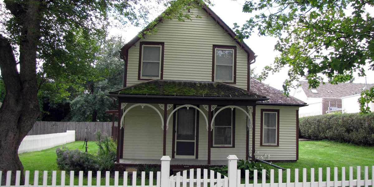 A yellow two story house has brown trim and Carpenter Gothic gingerbread on its front porch.