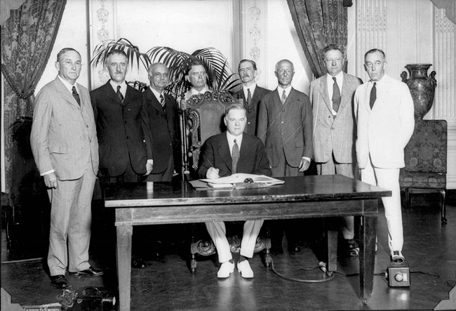 A group of men stand around a seated Herbert Hoover who poses as he signs a treaty.