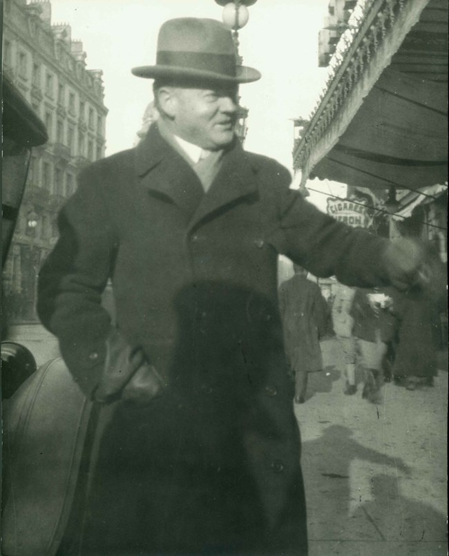 A man in a hat and overcoat walks a city street.