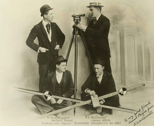 Four young men in 1890s clothes sit with their equipment for a surveying team portrait.