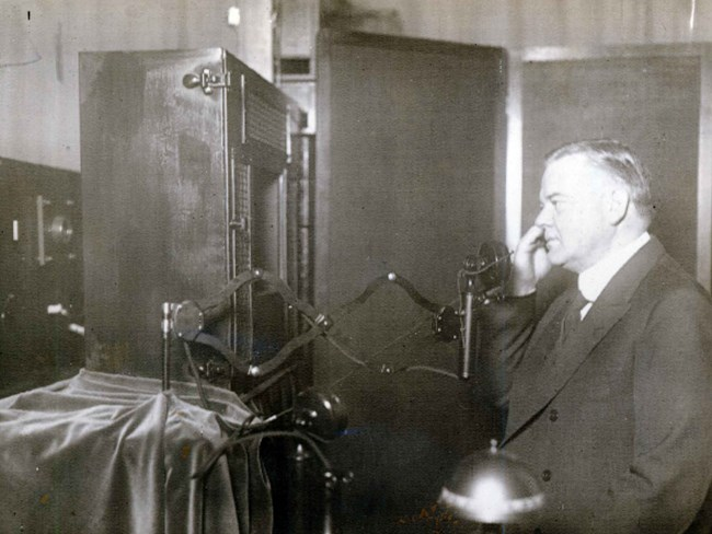 A man speaking by phone in front of a primitive television camera in 1927.