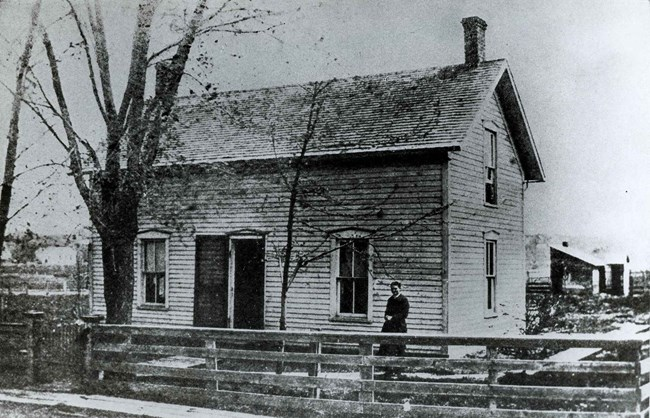 An 1880s photo shows a woman standing in the yard of her two story house.