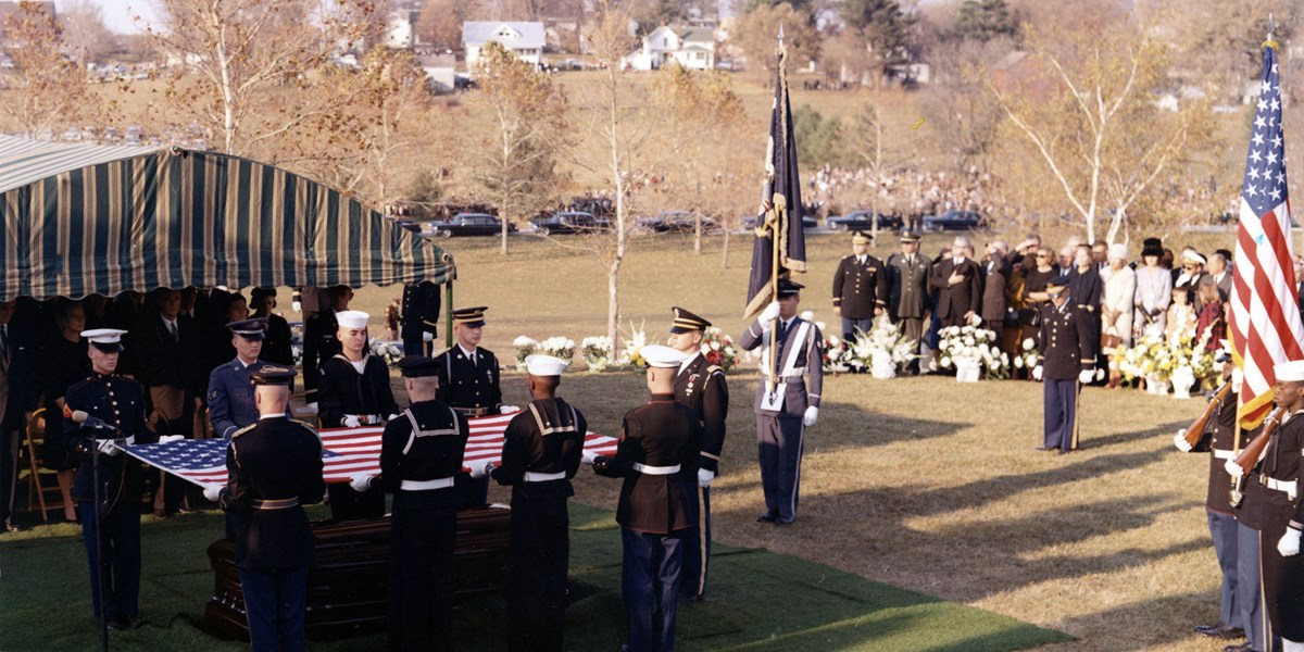 Mourners look on as American servicemen fold a flag over a coffin.