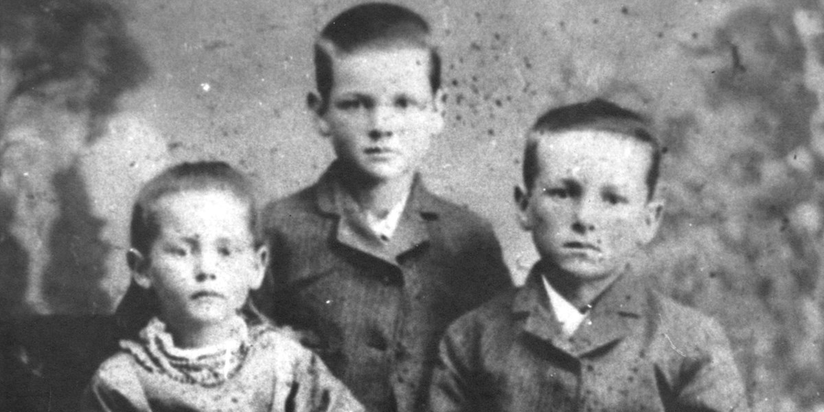 An eight year old boy poses for a portrait in 1881 with his younger sister and older brother.